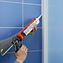 Hands holding a caulk gun and sealing the space between tile and a shower door.