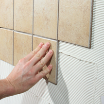 A hand is shown placing tan tiles onto a tile adhesive covered wall.