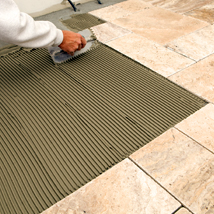 A person using TEC flooring products to install tile using mortars and additives.