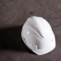 A white hard hat on a floor in need of surface preparation.