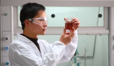 image of a scientist examining a beaker