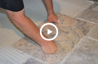 • Video Image: Video screenshot of a man using tile adhesive to install tile.