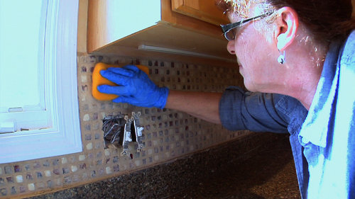 A woman taking a sponge over the freshly grouted and set backsplash tile.
