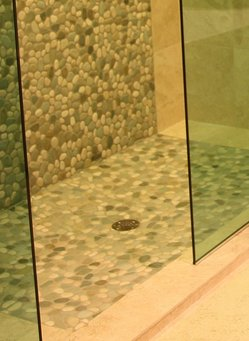 A shower floor with green tiles.