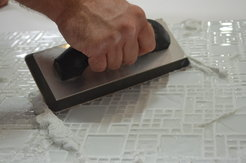 A hand using a trowel to apply grout to glass tile in a glass tile installation.