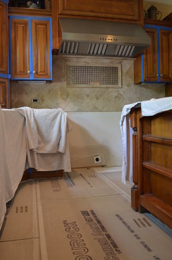 A kitchen covered in remodel sheets, painters tape around the cabinets, and cement board on the floor.