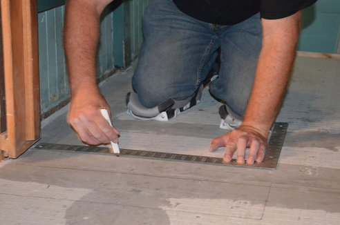 A man prepares for tiling a floor by dividing the floor into quadrants.