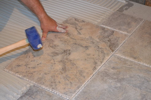 A person using a blue mallet to tap down the floor tile to ensure they are level.