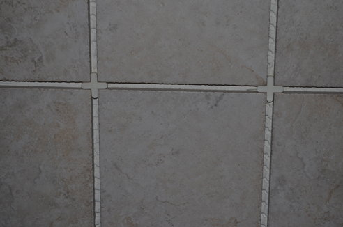Several grey tiles spaced perfectly with tile spacers.