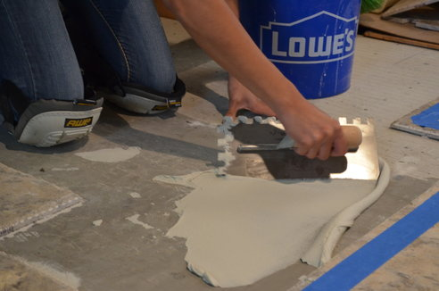 An image of a person using the flat edge of a trowel to apply tile floor mortar.