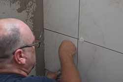 A man placing his fist against a tile while it bonds to a shower tile wall.