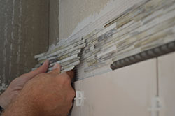 A hand bonds a square foot of tan mosaic tile to a shower wall.