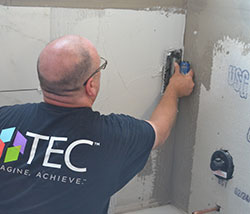 A man uses the flat end of a trowel to evenly spread shower mortar on a shower wall.