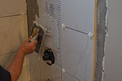 A man uses the comb end of his trowel to create even ridges in his shower mortar.