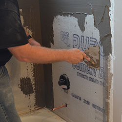A step in the waterproofing a shower process, coating the shower walls.