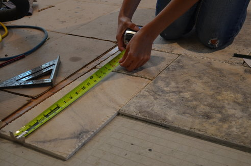 A person measures out tile while conducting a dry run of the floor tile installation layout.