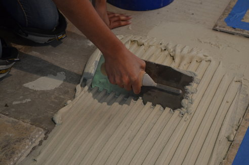 An image of a person combing tile floor mortar to form even ridges.