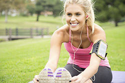 A young woman in athletic gear stretching and smiling because thinner cores allow her to move freely without leakage