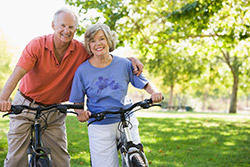 Older couple happily riding bikes because of adhesive technologies for stable thinner cores